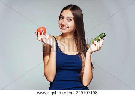 young beautiful sporty girl is watching her figure, smiling, holding a cucumber and a tomato