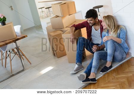 Young couple in love unpacking cardboard boxes at new home moving in concept