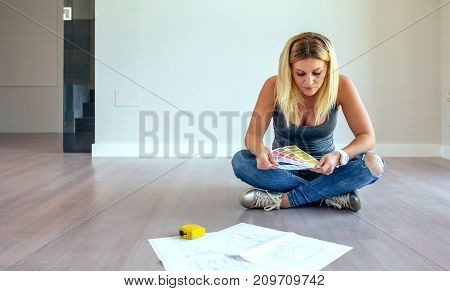 Girl looking color chart sitting on the floor