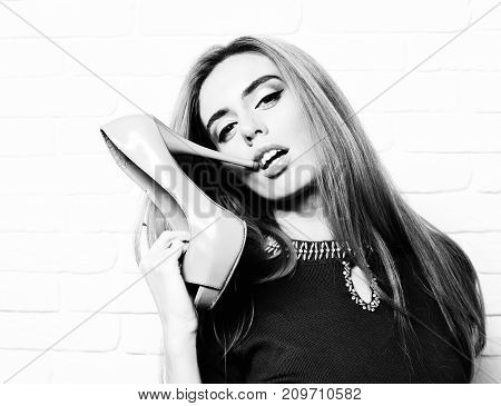 young fashionable sexy pretty woman or girl with beautiful long blonde hair on satisfied face in purple dress holding beige shoe or high heel near mouth on white brick wall background poster