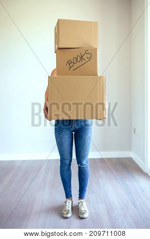 Unrecognizable woman carrying three moving boxes in living room