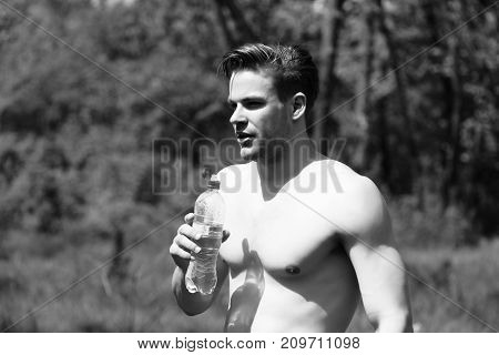 Sportive Macho Man With Naked Torso Drinks Water From Bottle