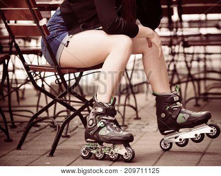Woman wearing roller skates sitting in town. Female being sporty having fun during summer time.