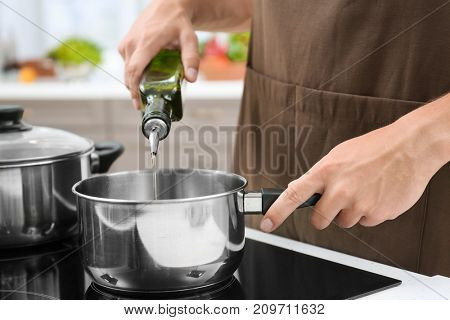 Man pouring cooking oil from bottle into saucepan on stove