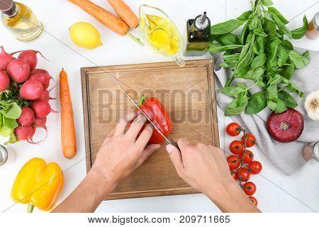 Man cutting bell pepper on wooden board