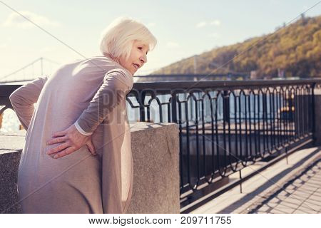 Unbearable pain. White-haired elderly lady standing on the bridge and touching her sore waist while suffering from pain