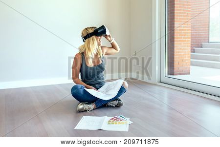 Young woman watching the decoration of her house with virtual reality glasses