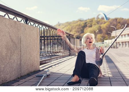 Unpleasant accident. Petite senior lady lying on the ground, having fallen down, raising one hand with a crutch and crying for help