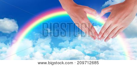 Woman making heart shape with hands against idyllic view of clouds against sky