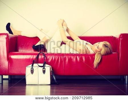 Woman Lying On Sofa Presenting White Bag