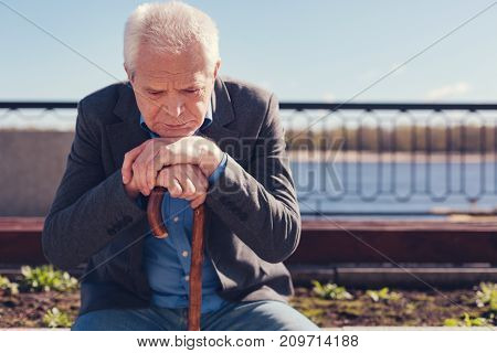 Disturbing thoughts. Downcast senior man sitting on the bench on the bridge, resting his chin on his hands folded on the cane and pondering some unpleasant issue