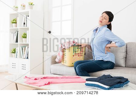 Pretty Young Woman Sitting On Sofa Stretching Body