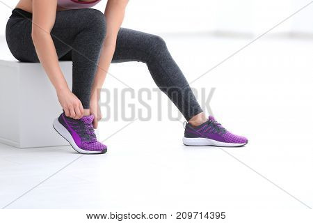 Young sporty woman tying shoelaces in gym