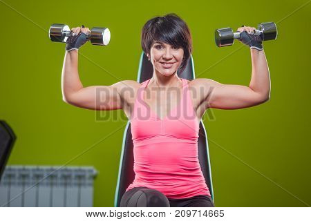 Gym woman strength training lifting dumbbell weights in shoulder press exercise. Female fitness girl exercising indoor in fitness center