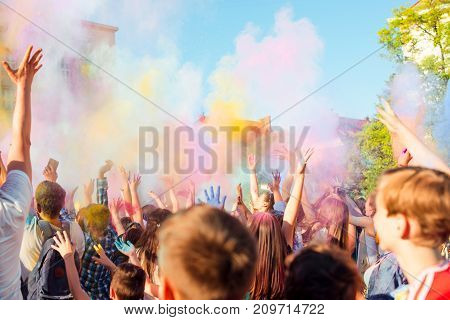 Young people having fun during Holifest throwing colorful powder in air