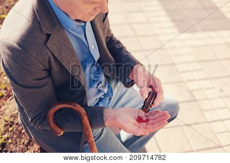 Following prescription. Good-looking senior man pouring red capsules from a bottle for pills into his hand while resting after a long walk