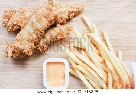 Chicken Nuggets, French Fries and Cheese Sauce Box on Wooden Board Plate Background. Typical fast food meal, unhealthy eating and high fat and calories products concept, simple image with empty copy space.