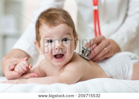 Pediatrician female doctor examines baby boy with stethoscope checking heart beat