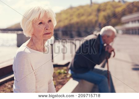 Wistful looks. The focus being on a charming white-haired senior woman thinking about something disquieting while her husband sitting at a distance and being immersed into his own thoughts