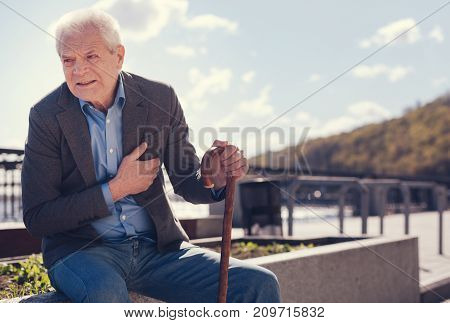 Worrying symptoms. Handsome white-haired man sitting on a concrete edge of a flower bed and suffering from a dull chest pain while wincing