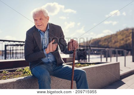 Unbearable angina. White-haired senior man sitting on a concrete edge of a flower bed, holding a cane and suffering from angina