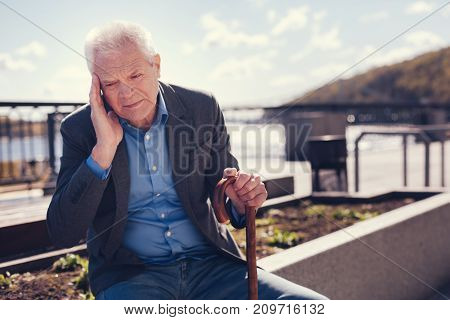 Unbearable migraine. Well-dressed elderly man sitting on a concrete edge of a flower bed and wincing and touching his temple while suffering from a splitting headache