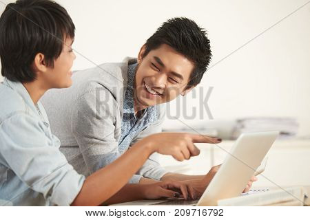 Laughing students discussing something funny on laptop screen