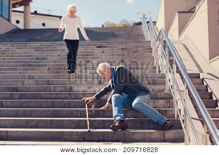 I will help. Petite loving senior lady running down the stairs, trying to help her husband to get up after falling down the stairs