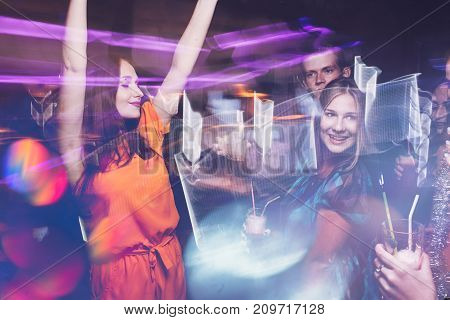 Happy New Year dance party in motion. Joyful friends company in night club, active Christmas celebration. Disco people in blurred colors, modern youth life