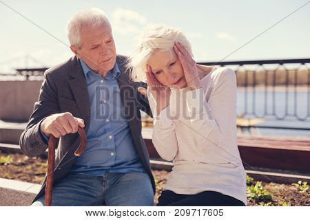 Worried husband. White-haired elderly man sitting next to his beloved wife and looking at her worriedly while she pressing hands to her temples, suffering from a splitting headache