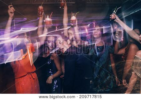 Happy company on dance floor. Joyful New Year in night club, active Christmas celebration in motion. Disco party in blurred colors, modern youth life, pickup concept