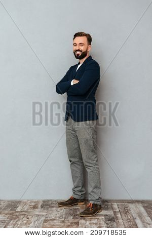 Full length image of bearded man in business clothes posing with crossed arms and looking at the camera over gray background