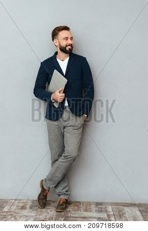 Full length image of happy bearded man in business clothes holding laptop computer and looking away over gray background