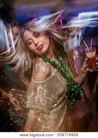 Female in night club in blurred motion. Stylish lady at Christmas discotheque, New Year company, modern youth life