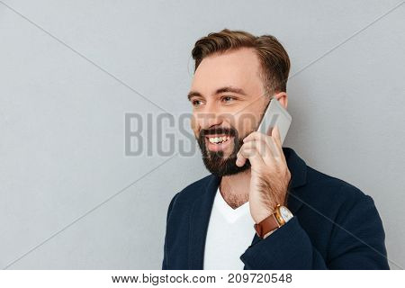 Portrait of handsome bearded man in official clothes talking on smartphone isolated over grey