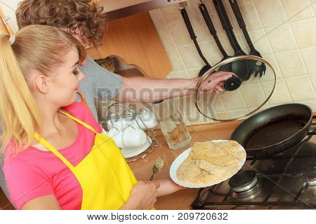 Couple frying breaded chicken cutlet on fry pan. Couple woman and man making dinner meal.