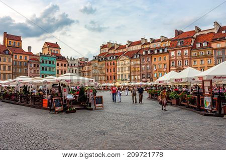 WARSAW, POLAND - JUNE, 2012: Beautiful view of Old Town market place on sunny day with lots of tourists