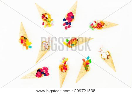 Waffle cones with colorful bright candy on white background. Food pattern. Flat lay, top view