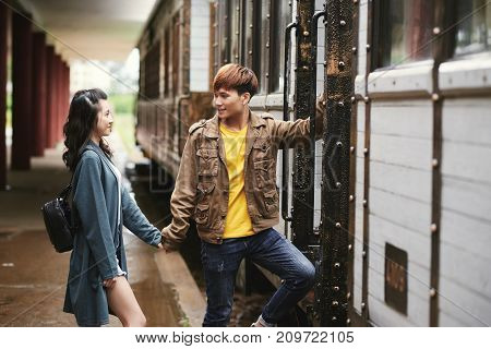 Vietnamese young couple holding hands and getting on the train