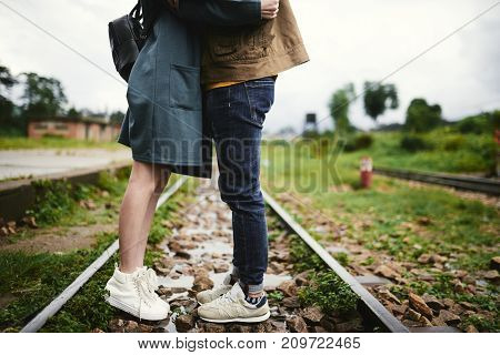 Cropped image of kissing couple standing on railway