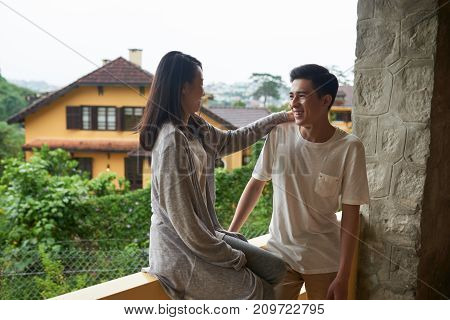 Young Vietnamese couple laughing and chatting on balcony