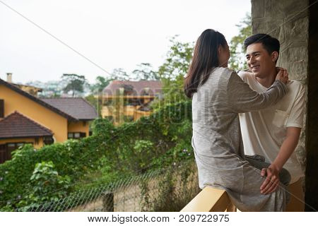 Young Asian couple on vacation standing on hotel balcony