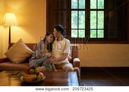 Young Asian man kissing his wife on forehead when they are sitting on sofa