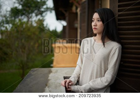Young woman deep in thoughts standing on balcony