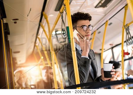 handsome young businessman in eyeglasses talking on smartphone and drinking coffee in bus