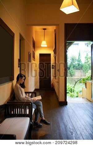 Young Asian woman sitting on bench in hotel hall and reading a book