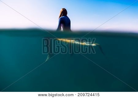 Surfer is sitting on surfboard in ocean. Surfer and ocean