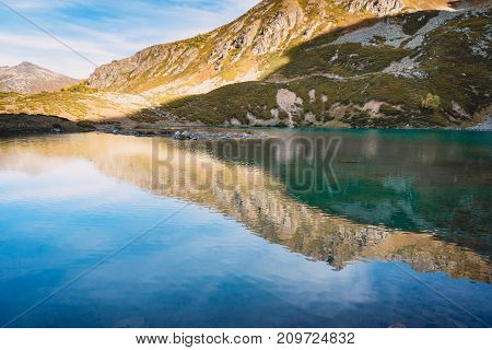 Reflection of mountains on the lake. Beautiful mountain lake with turquoise water. Mountain landscape.