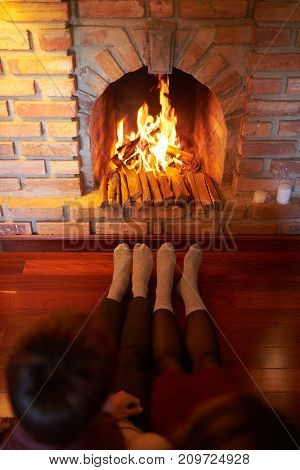 Couple in socks warming feet at fireplace in living room