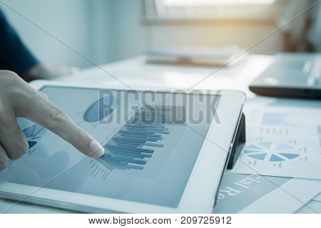 Profit graph of stock market indicator with hand touching tablet for check data or graph invesment. Abstract stock data concept. Stock financial statistic graph analysis. Strategy plan finance concept